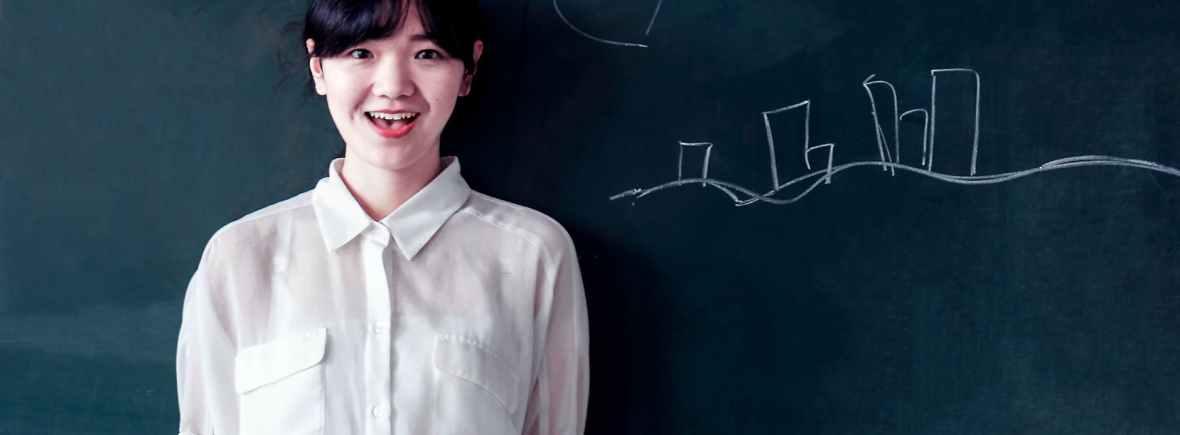 黒板の前で話す女の先生